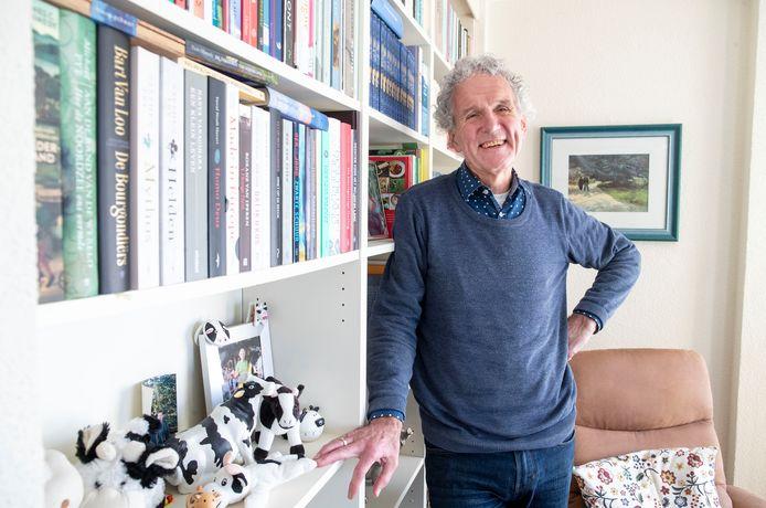 Kees van Heerikhuize, de omgevallen boekenkast, bij de boekenkast in zijn woonkamer.