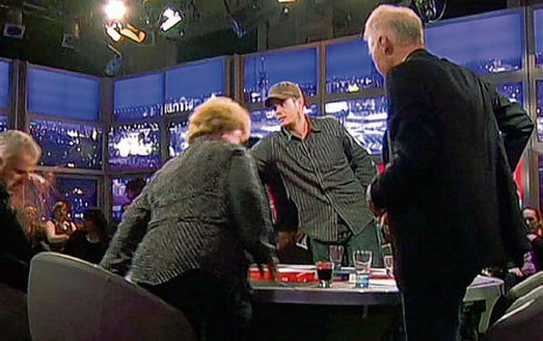 Joran van der Sloot (met pet) gooit vlak na de uitzending van Pauw en Witteman een glas wijn in het gezicht van Peter R. de Vries. Beeld NPO