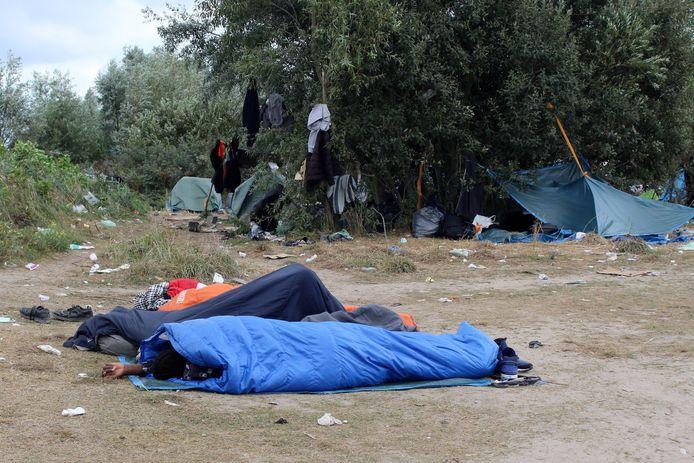 Des migrants dorment dans des sacs de couchage dans un camp de migrants de fortune près de l'hôpital de Calais, en France, le 10 septembre 2021.
