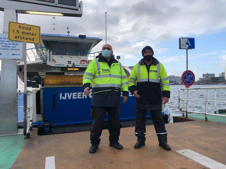 Appie en Johan zorgen ervoor dat iedereen een mondkapje draagt op de pont. Beeld Wouter Laumans
