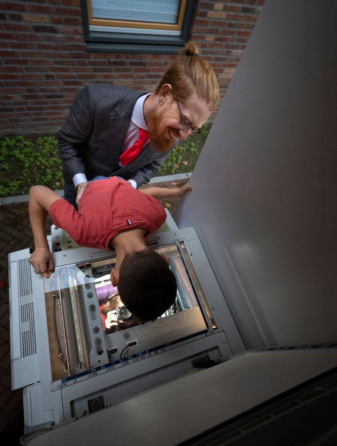 Yessin (7) legt begeleid door de interactieve straatartiest Vince Linders zijn gezicht op het kopieerapparaat en ziet tot zijn verbazing Sophie van Krieken vanuit het apparaat een foto maken.