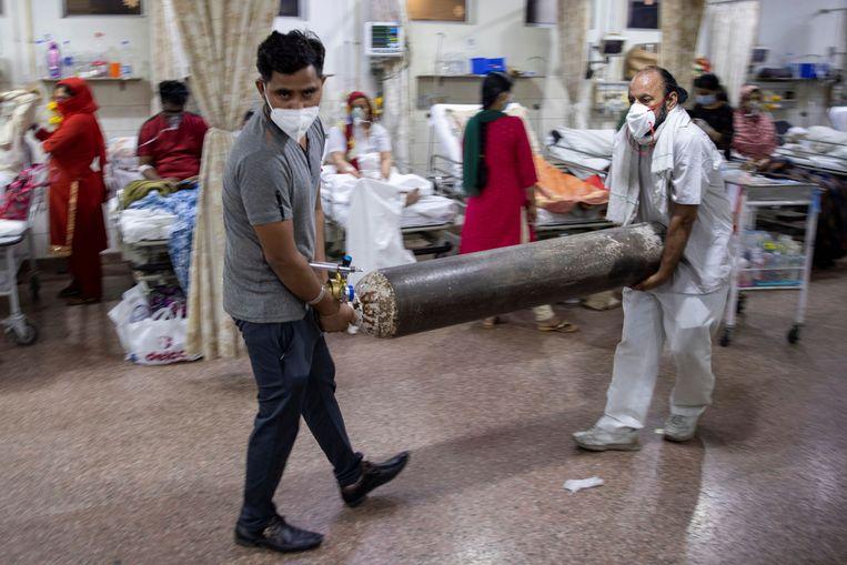 Familieleden van een coronapatiënt komen zuurstof brengen in een ziekenhuis in India. Beeld REUTERS