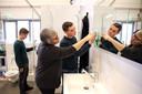 Bram (links) en Boaz leren in de nagebouwde woning de badkamer schoonmaken.