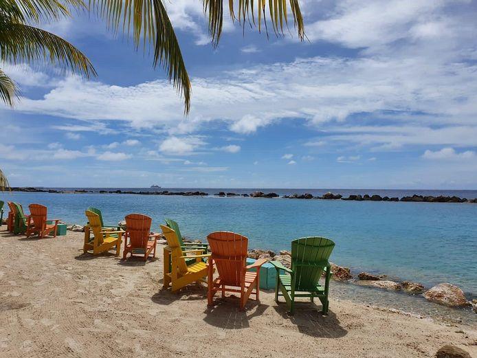 Lege loungestoelen bij een strandje.