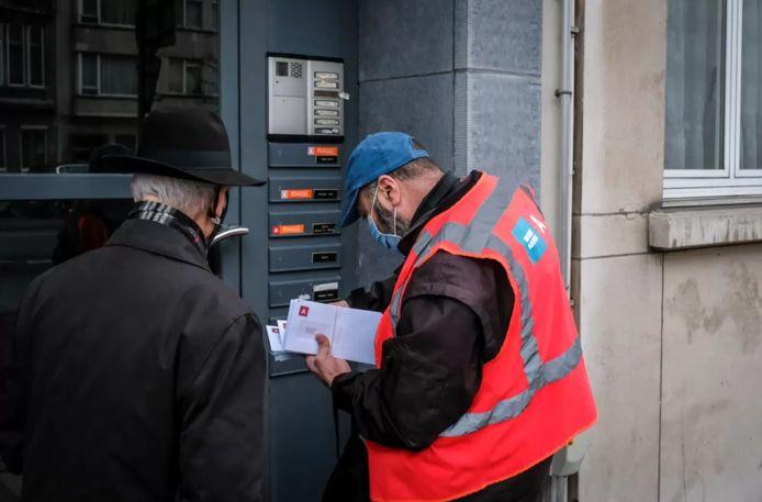 Een ambtenaar van de Stad Antwerpen bust de brieven met de test-uitnodiging in de buurten rond de Belgiëlei en de Lange Leemstraat.