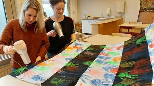 Mandy van Vugt en Carlijn Spanjers, verkeersouders van De Kiem, föhnen de verfhanden op het spandoek droog.
