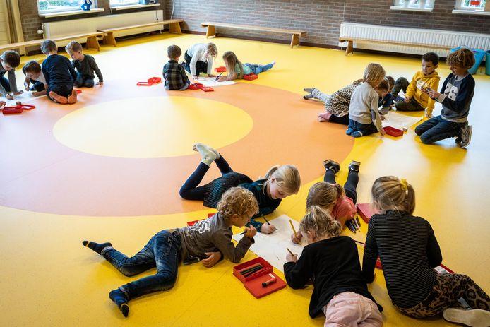 Leerlingen tekenen in de lokalen van de Generaal Van den Boschschool nadat regen het stoepkrijten buiten onmogelijk maakte.