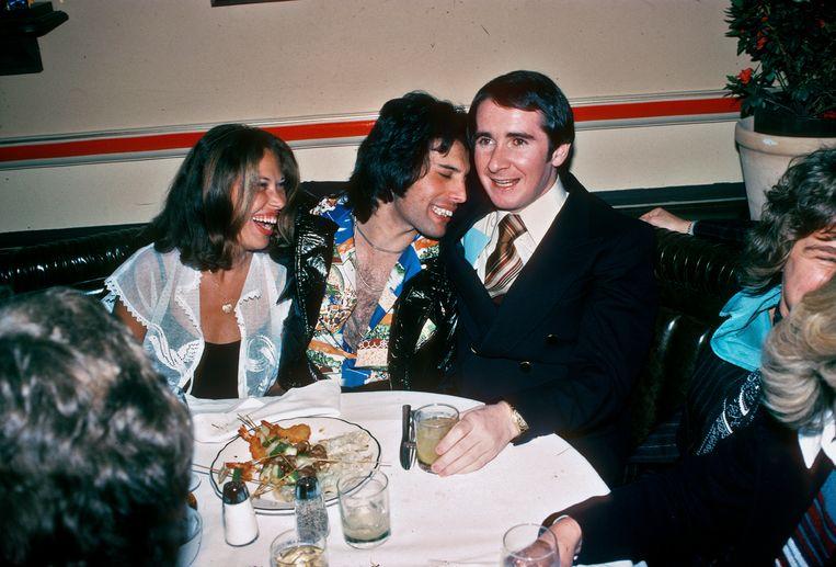 Freddie Mercury (midden) aan tafel met John Reid (rechts), 1977. Beeld Getty Images