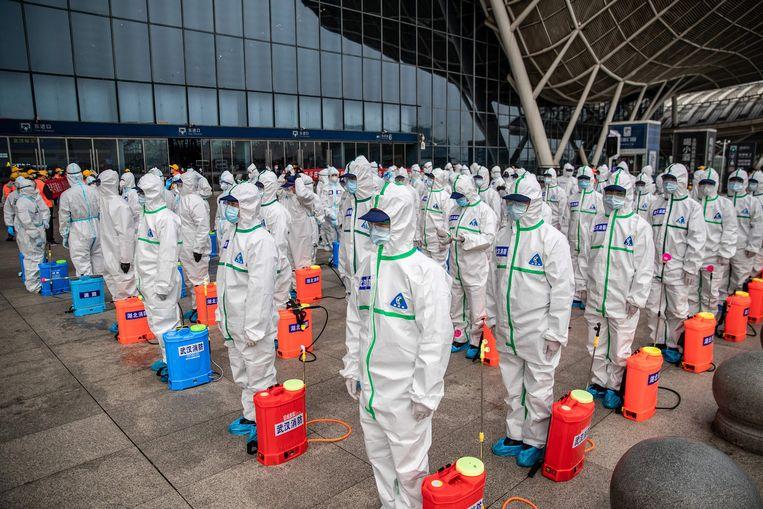 Personeel staat in het gelid, klaar om het station van de Chinese stad Wuhan te ontsmetten.  Beeld AFP