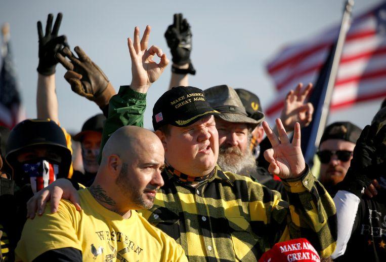 Leden van de extreemrechtse beweging Proud Boys die Donald Trump onvoorwaardelijk steunen, maken bij een betoging in Washington met de hand een ok-teken, en verwijzing naar witte suprematie. (REUTERS/Jim Urquhart) Beeld REUTERS
