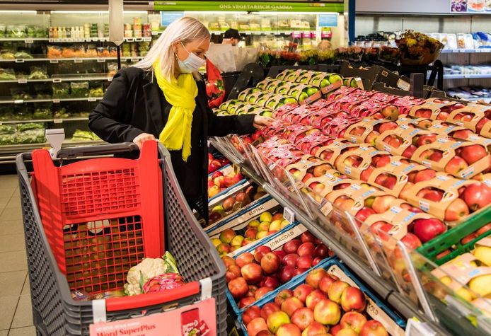 Een vrouw winkelt in de Delhaize.