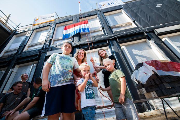 De oudste en de jongste leerlingen - Carlos, Marit, Jesse en Thijs - hijsen samen met directeur Renate van Iersel de vlag bij de nieuwbouw.