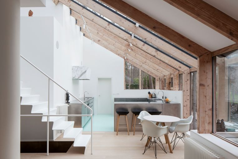 LOW-architecten verving de bestaande trap door dit luchtige, witte exemplaar. De keuken werd vergroot en kreeg een zeegroene gietvloer in polyurethaan.   Beeld Johnny Umans