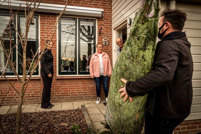Cecile en Peter Gelissen ontvangen de kerstboom uit handen van Jan van Gestel (r) en Marieke van Dijk (l).