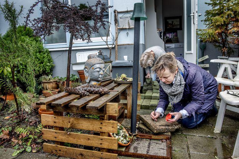 Onderzoekster Sytske de Waart zoekt in Amsterdam Noord bij bewoonster Liesbeth  naar landpaltwormen. Beeld Jean-Pierre Jans