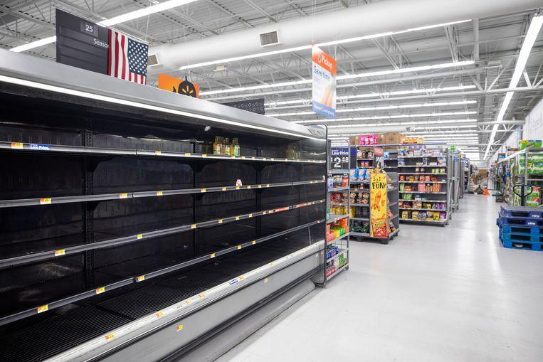 Lege schappen in de Walmart waar normaal sinaasappelsap staat. Beeld EPA