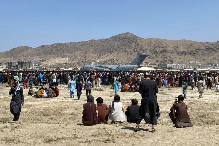 Honderden mensen probeerden gisteren in een Amerikaans militair toestel te klimmen op de luchthaven van Kabul.  Beeld AP