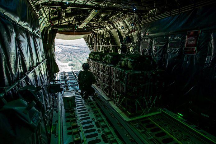 Zogeheten 'container delivery systems' staan in het geopende laadruim van een vliegende C-130 transportvliegtuig klaar voor dropping.