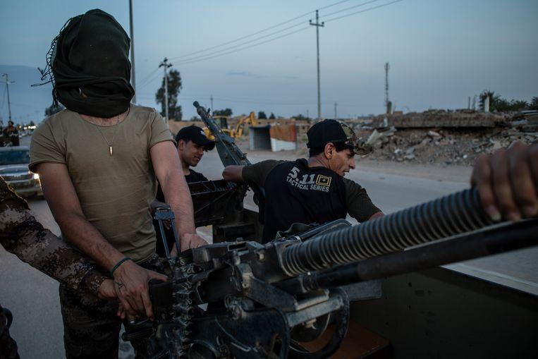 Een konvooi van de 'hashd al shaabi' (volksmilities) in de stad Al Qaim, vlak bij de grens met Syrië. Beeld Hawre Khalid