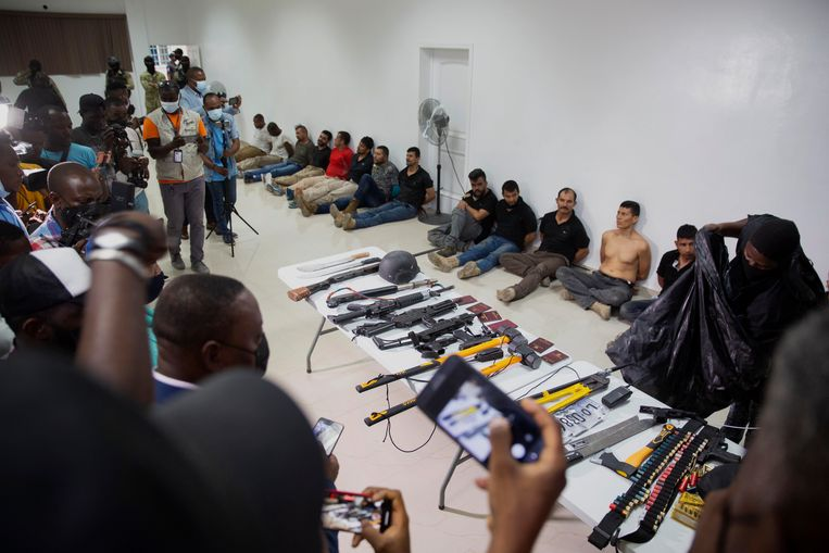 Tijdens een persconferentie op het hoofdbureau van de nationale politie donderdagavond in de hoofdstad Port-au-Prince werden de zeventien arrestanten getoond, evenals een hoeveelheid in beslag genomen wapens van de mogelijke daders van de moord op de Haïtiaanse president Jovenel Moïse. Beeld AP