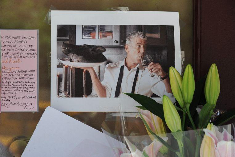 Mensen leggen bloemen, foto's en berichten bij het restaurant van Anthony Bourdain. Beeld Photo News