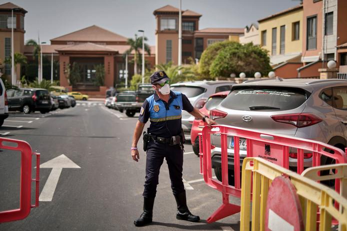 Een Spaanse politieagent sluit de toegang tot het H10 Costa Adeje Palace hotel op Tenerife af.