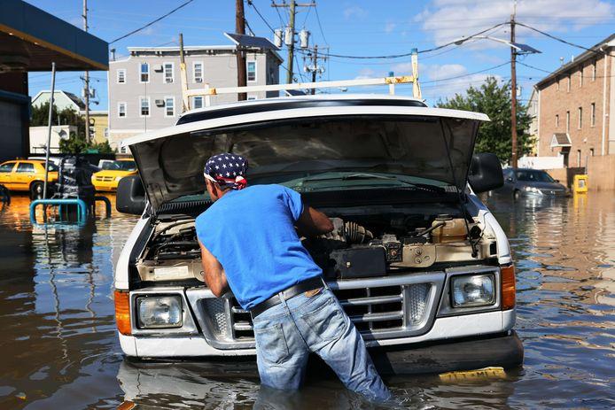 Een man probeert zijn ondergestroomde wagen te herstellen in Newark, New Jersey.