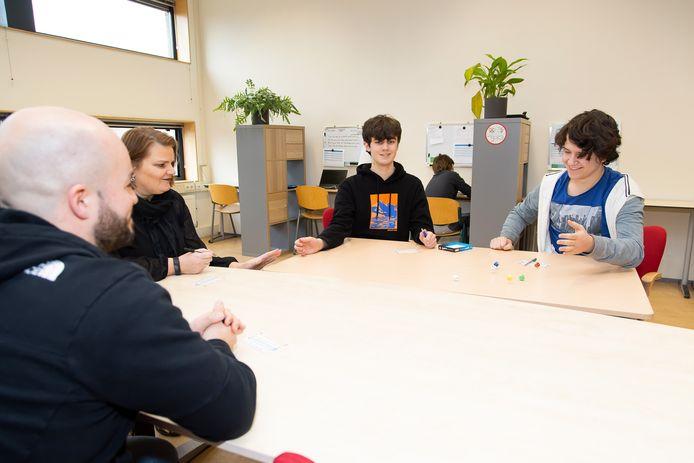 Koen en Kyran spelen een spelletjes met orthopedagoog Carla van Moorsel en docent Roel Derksen