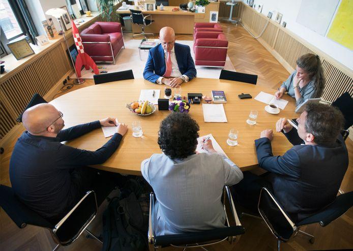 Minister Grapperhaus wordt geinterviewd door leden van de onderzoeksredactie. Behalve de minister en zijn voorlichter (rechts op de foto) zie je van links naar rechts (op de rug gezien) Thomas Muntz van onderzoeksplatform Investico, Wout van Arensbergen (ED) en Hessel de Ree (BN De Stem).