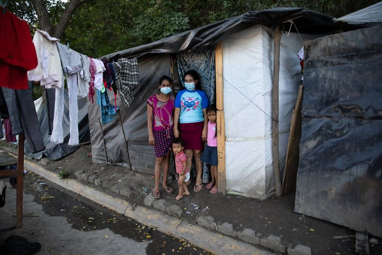Elida Madrid (midden) met dochter Marina (links) en diens twee kinderen voor hun provisorische woning langs de autoweg.  Beeld Tomás Ayuso