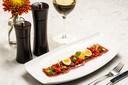 Carpaccio van gerookt vlees met olijvencrumbles, kwartelei, paprikasaus en chips van parmiggiano