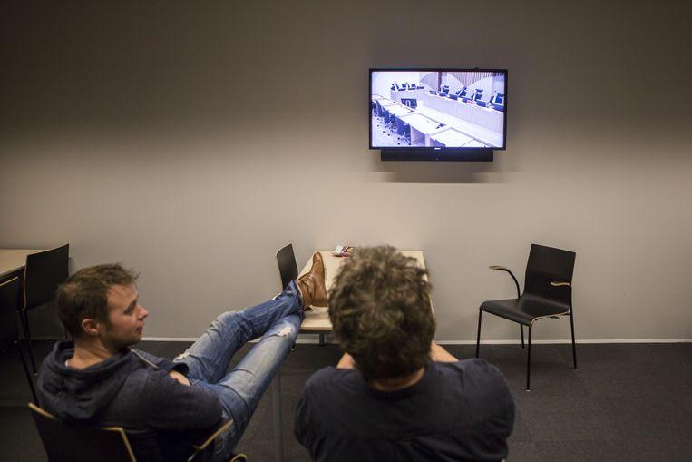 Journalisten volgen de rechtszaak via een televisiescherm in een andere zaal. Beeld Julius Schrank