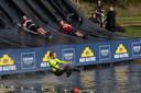 Deelnemers aan Mud Masters plonzen in het water.