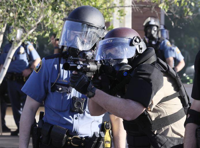Een soldaat van de nationale garde richt zijn geweer op de demonstranten in Minneapolis.