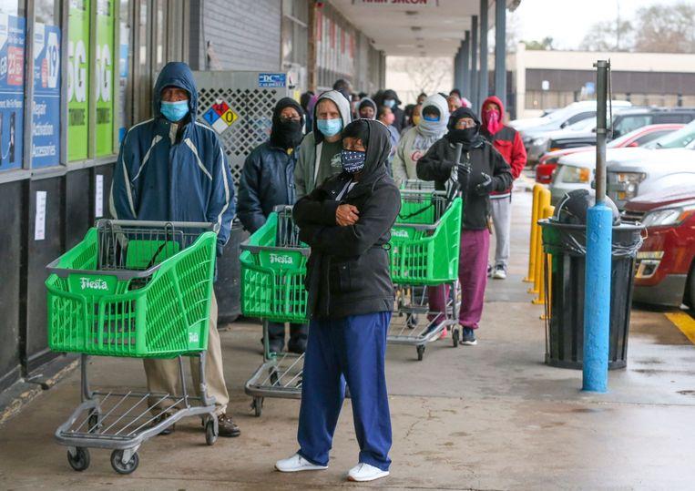 Klanten in februari in Houston (Verenigde Staten) in de rij voor een winkel die weer open mocht na opheffing van de coronarestricties. Beeld AFP