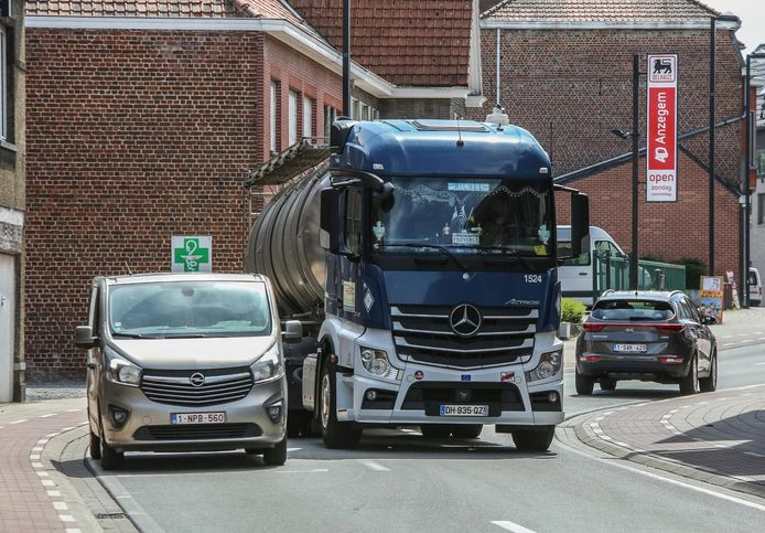 Een truck rijdt langs een geparkeerde wagen in de Kerkstraat. De omleidingsweg moet dit vermijden.