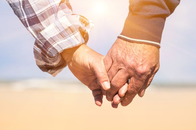Senior couple in love walking at the beach holding hands in a romantic sunny day - Concept of love and family union Beeld Thinkstock