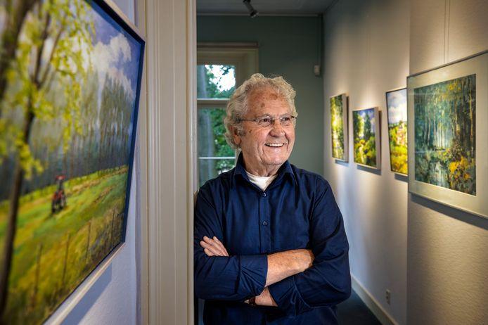 Nuenenaar Jan Vlemmix tussen zijn schilderijen op de tentooonstelling.