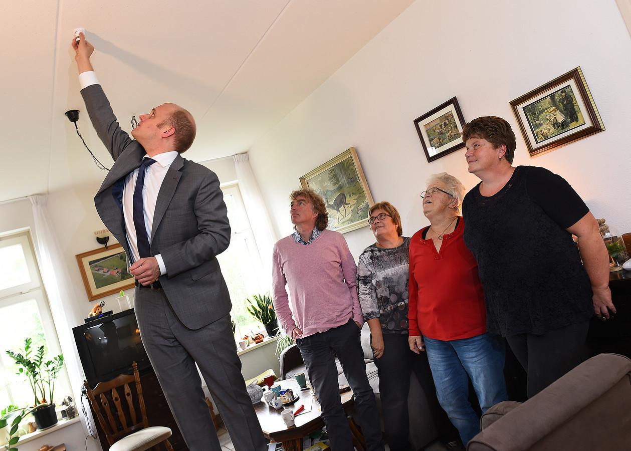 Burgemeester Joris Bengevoord van Winterswijk zet de slimme rookmelder aan in het huis van Willemien Westerveld (tweede van rechts).
