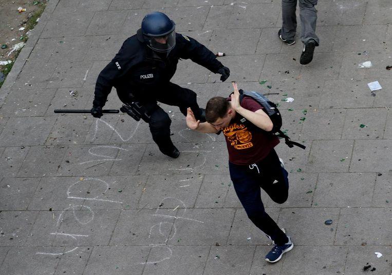 Een lid van de oproerpolitie gaat achter een demonstrant aan. Beeld epa