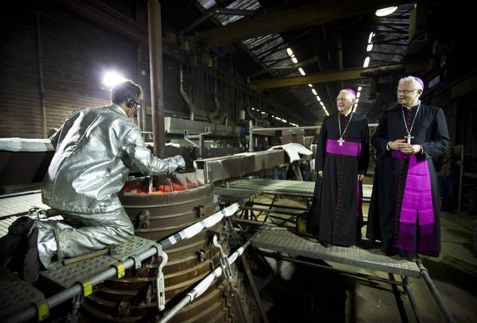 De bisschoppen Hurkmans van Den Bosch (l) en Hoogmartens van Hasselt kijken toe bij de laatste handelingen na het gieten. foto Ilvy Njiokiktjien/ANP