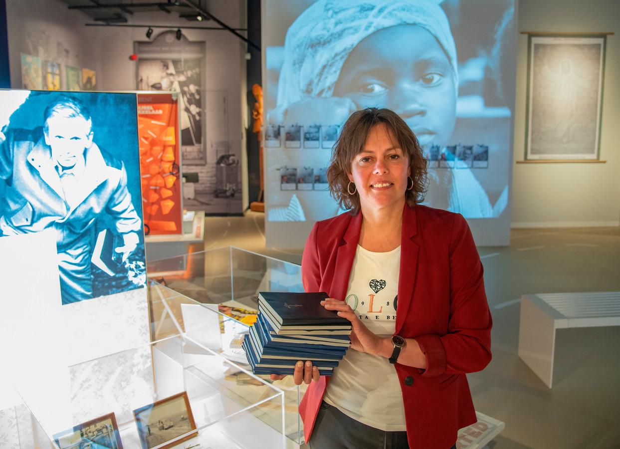 Marjon Snel van Open Doors laat een stapel bijbelvertalingen zien in het minimuseum over de 65-jarige historie van de organisatie.