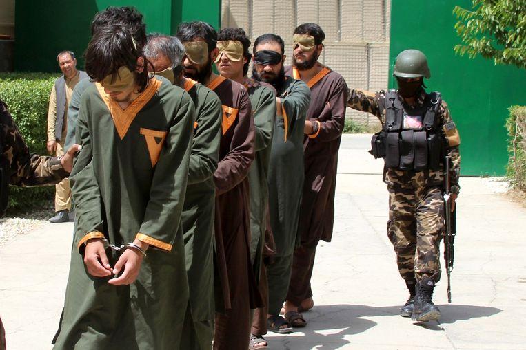 Afghaanse veiligheidsagenten tonen gearresteerde Taliban, in Ghazni, een stad in Zuidoost-Afghanistan afgelopen mei.  Beeld EPA