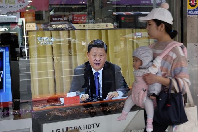 Een bewoonster van Taipei passeert een etalage met een tv waarop net Xi's zorgwekkende toespraak wordt uitgezonden.