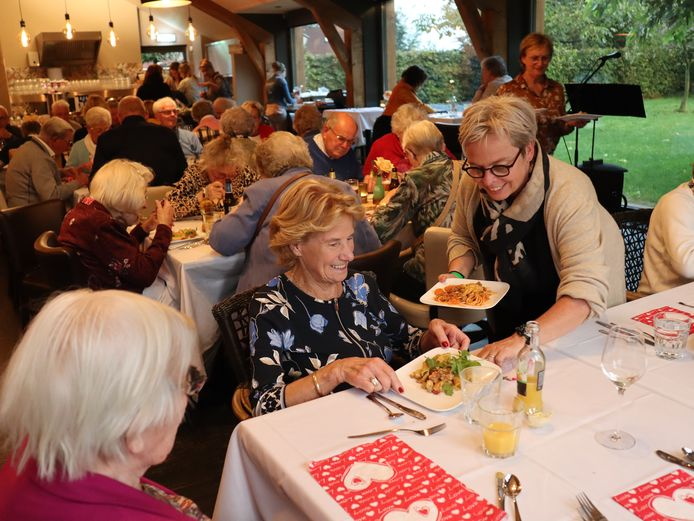 Esther de Bie brengt Riek Simons haar hoofdgerecht klaargemaakt door de dames van Ladies' Circle 41 de Leijgraaf.