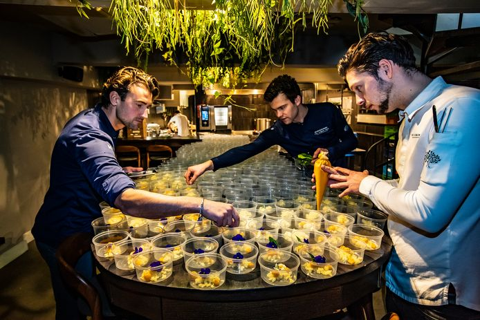 Kevin Schlaman (r), Nino Boot en Valentijn Bergers (l) van het Deventer restaurant The Lemon Tree zijn druk met hun in coronatijd ontwikkelde maaltijdbox. Gedeputeerde Eddy van Hijum  roemt die ondernemersgeest.