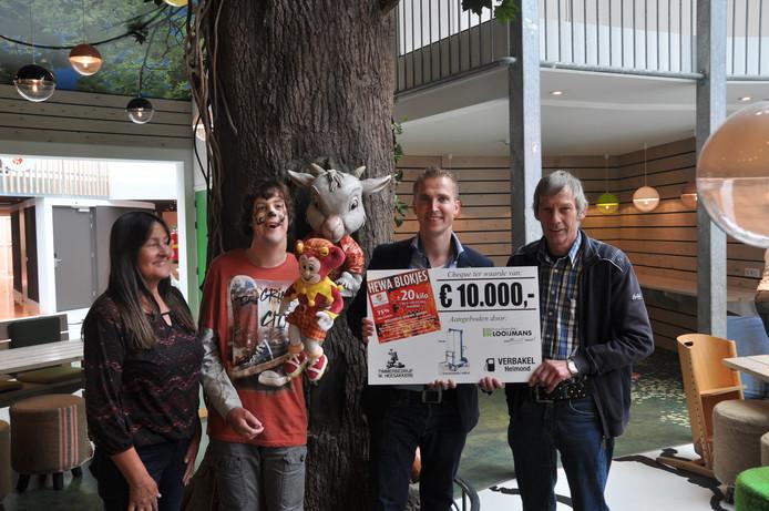 Willy Heesakkers (rechts) overhandigt zijn cheque. Van links naar rechts staan zijn vrouw Annie, zoon Tim en Gert-Jan van Boxtel van Villa-Pardoes.
