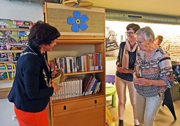 Burgemeester Marga Vermue (l) opende vorig jaar een kast vol informatiemateriaal over dementie, bij ontmoetingscentrum JOTA in Oostburg. Bestuursleden Dementievriendelijk Sluis Karien de Vriese (m) en Linda van de Velde (r) hielpen mee