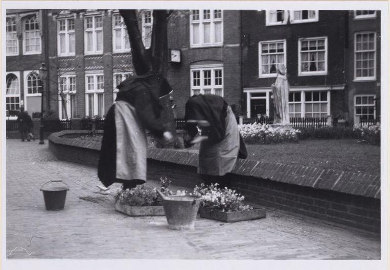 Nog elk jaar op 2 mei wordt het graf van Cornelia Arens (gestorven in 1654) versierd met bloemen. Hier doen twee van de laatste begijnen dat, ergens in de jaren zestig. Beeld Stadsarchief