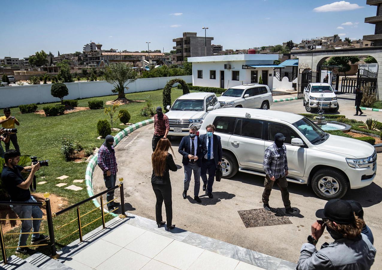 Koerdische beveiligers kijken toe als onder meer de Nederlandse gezant voor Syrië Emiel de Bont arriveert (links van de twee mannen in het midden).